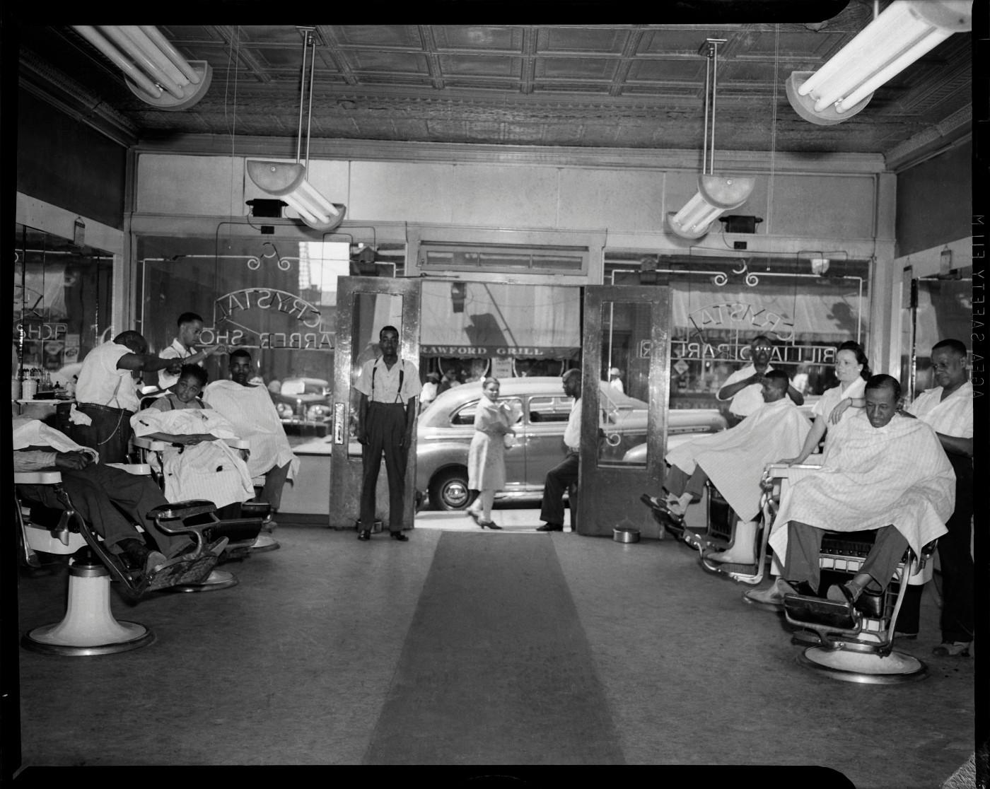 "Charles ""Teenie"" Harris, 'Barbers at work in the Crystal Barber Shop with view of Crawford Grill No. 1 through front door,' c. 1949"
