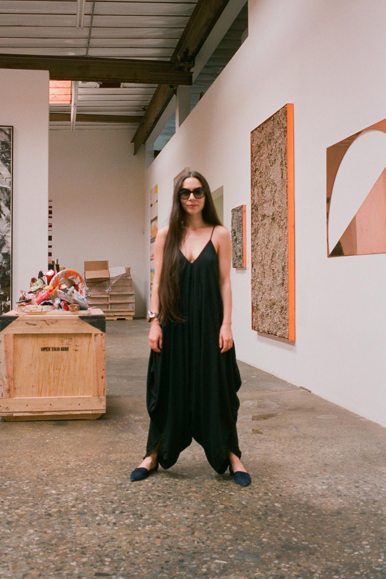 Walead Besht photograph portrait of a woman in large sunglasses and chic black outfit in an art gallery