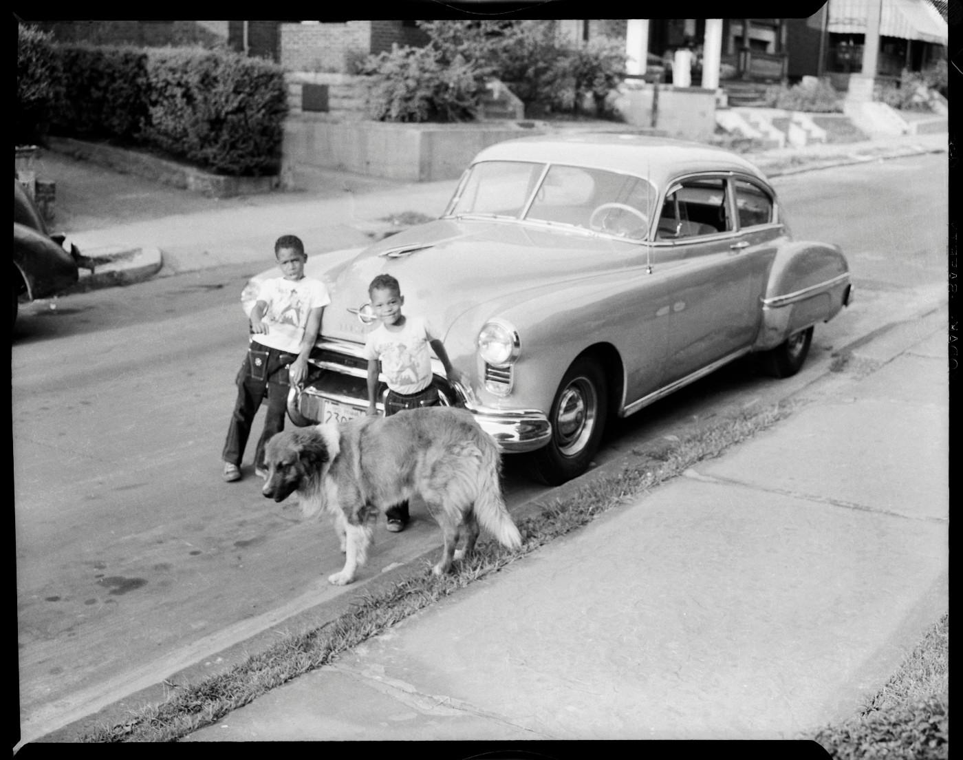 "Charles ""Teenie"" Harris, 'Ira Vann Harris and Lionel Harris with their dog ""Joby"" standing in front of parked car, on Mulford Street, Homewood,' c. 1952"