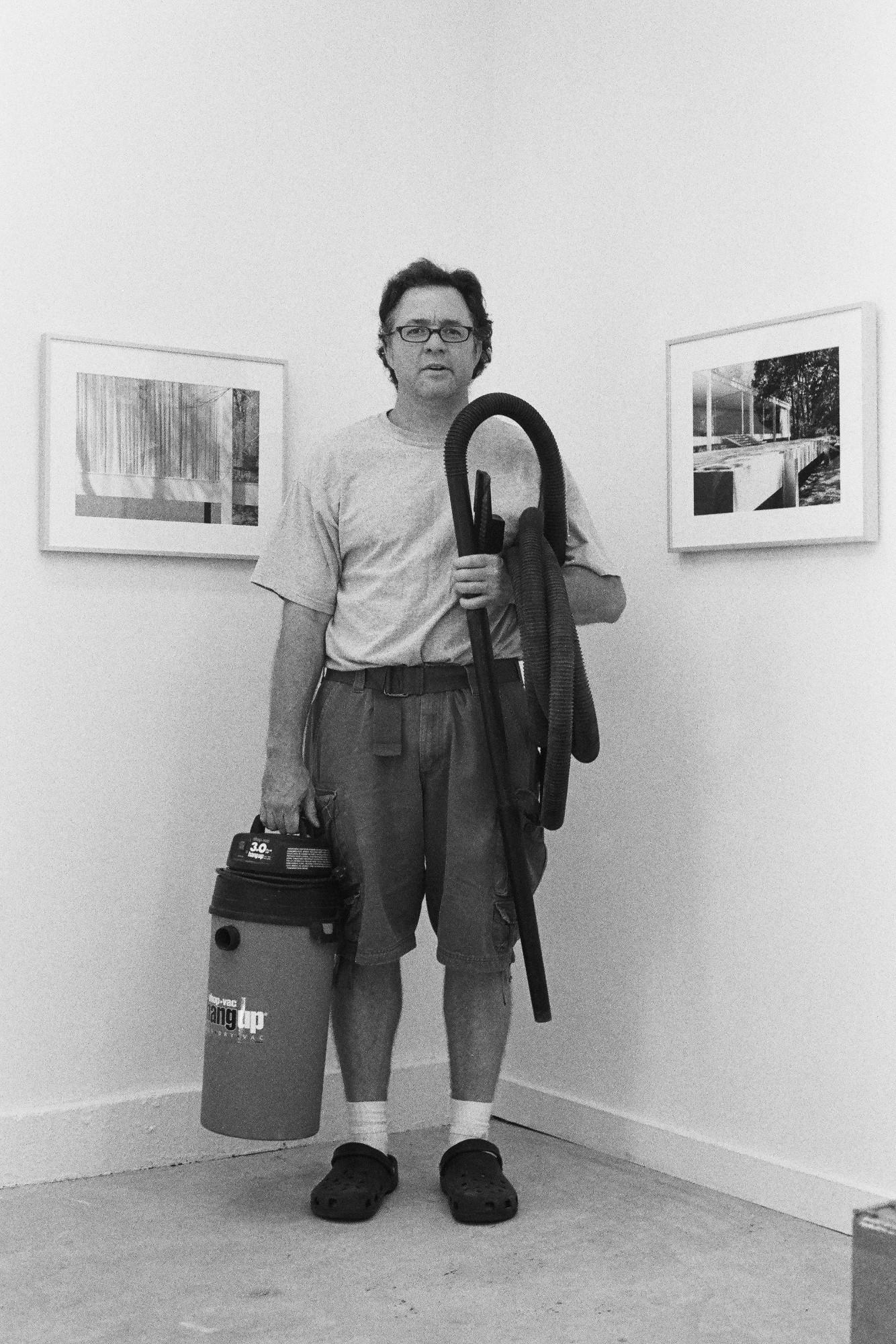 Walead Besht portrait photograph of a man in t-shirt and jeans holding a vacuum in a gallery