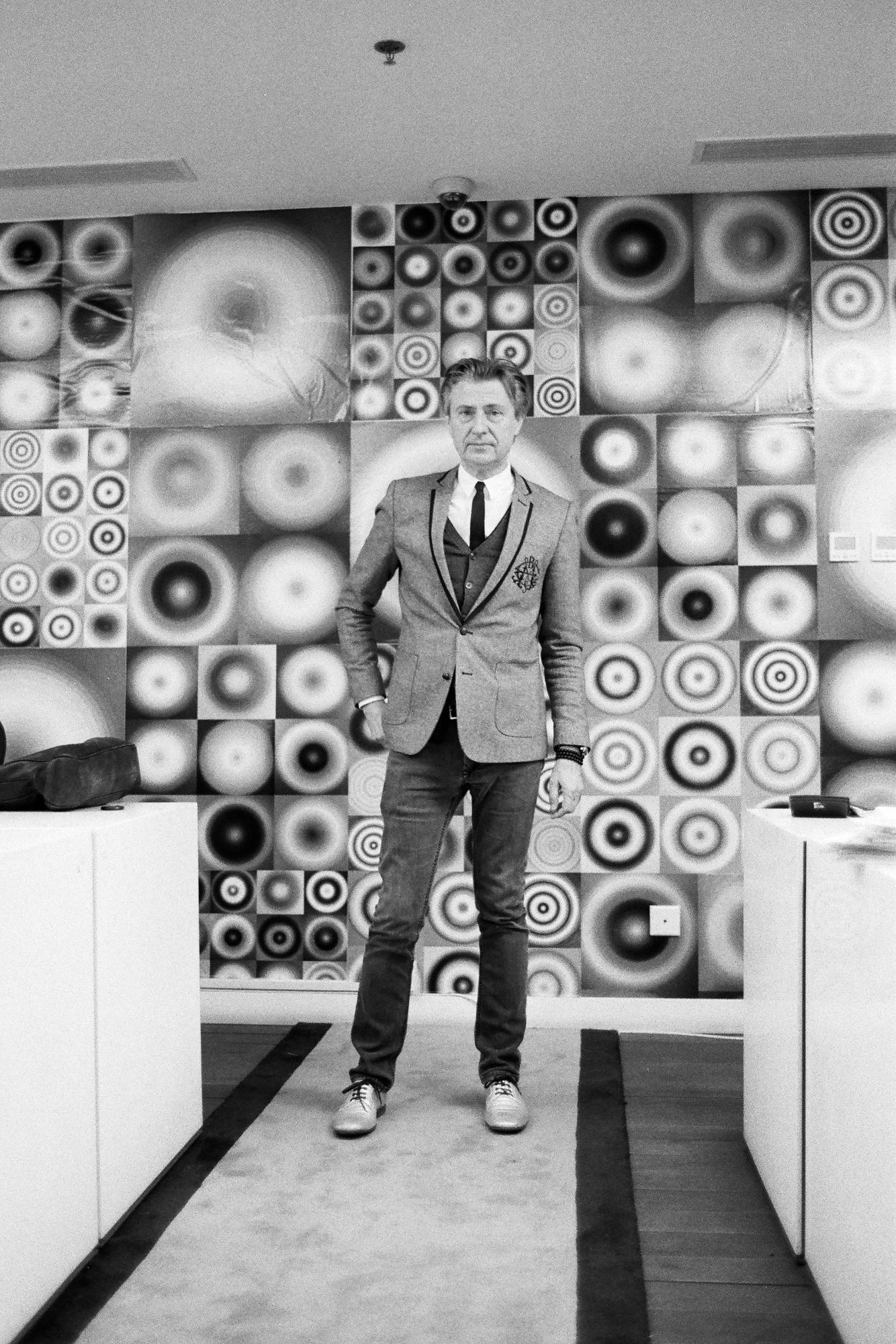 Walead Beshty photograph portrait of a man in a fitted suit in front of wall of art