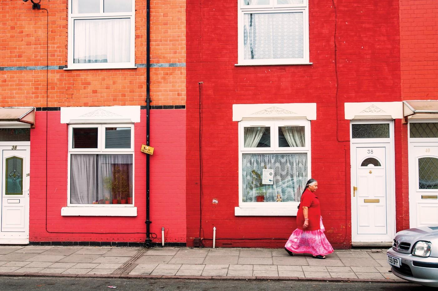 "Pablo Bartholomew, ""Gujarati Woman in a Saree Walks Past Red Brick Homes in her Neighborhood, Leicester, UK,"" 2011"