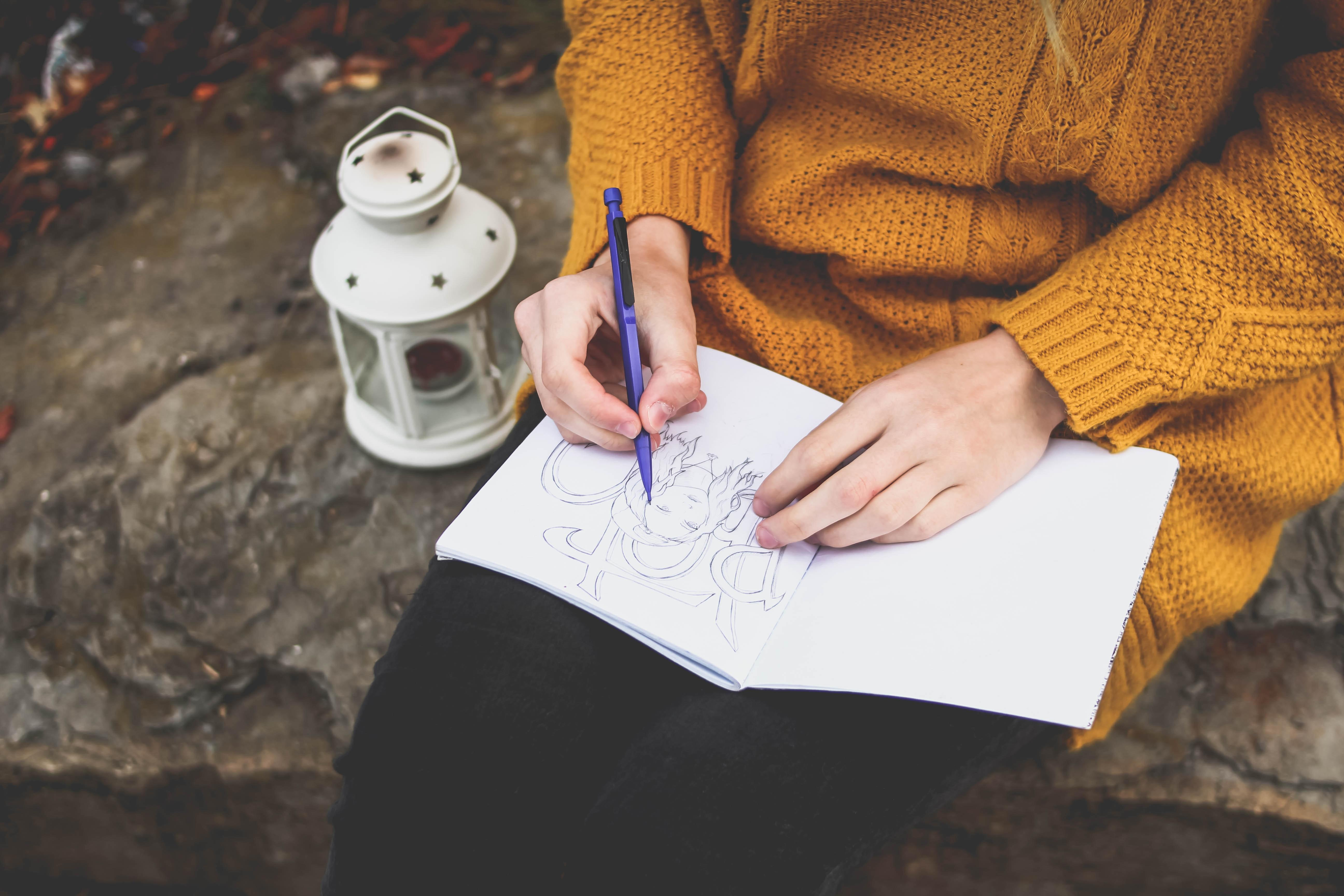 a photo of a person drawing in a journal