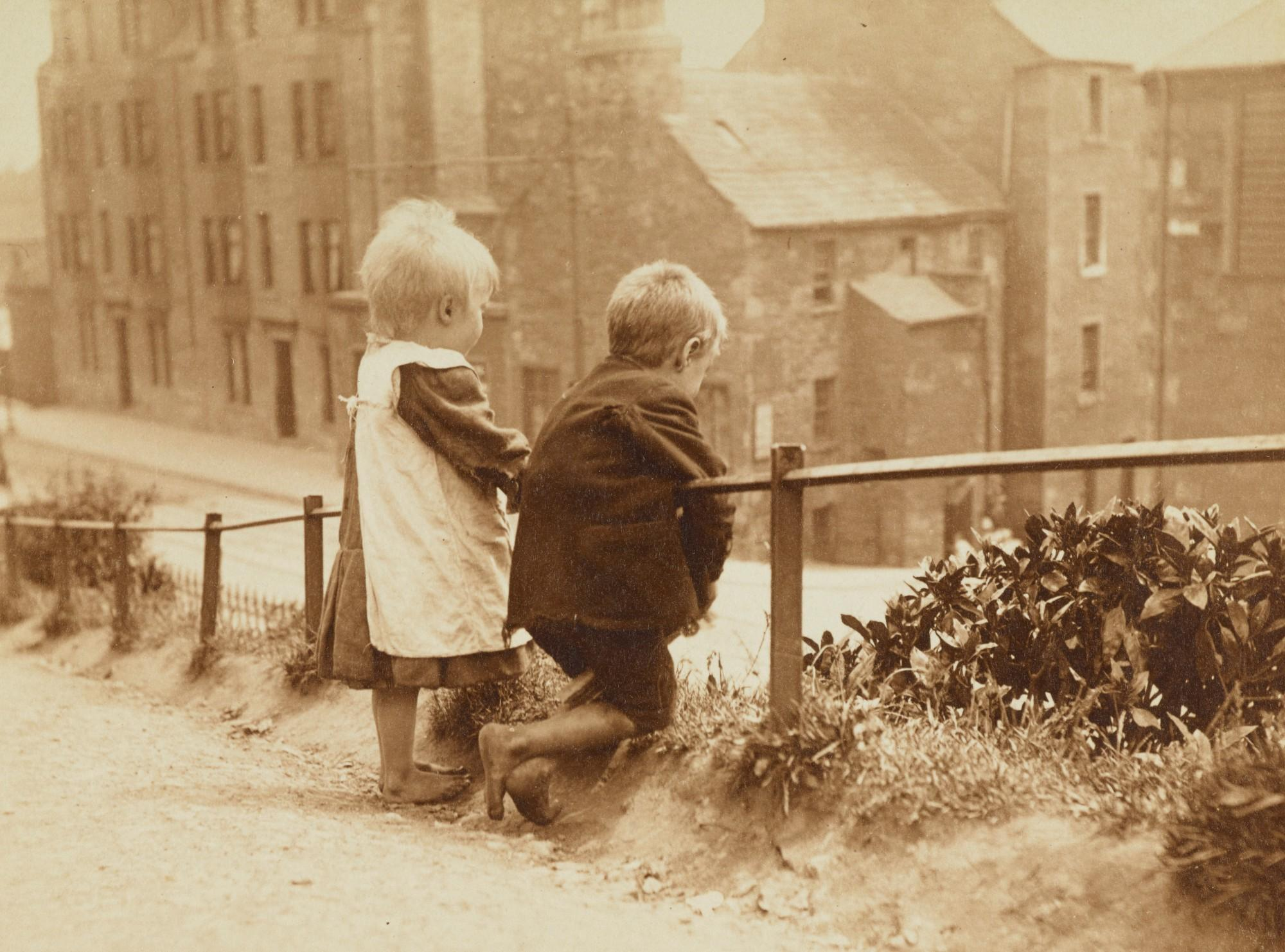 small children look down at a city block