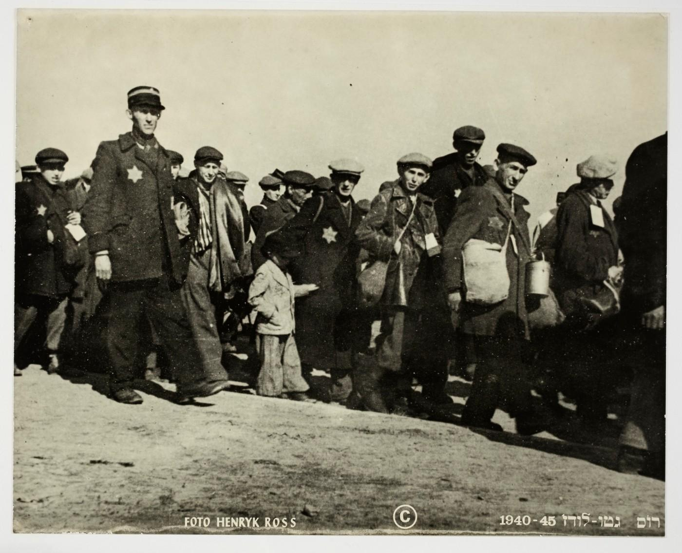 Henryk Ross, Deportation, people walking looking at camera, small boy in center escorted by Ghetto police, 1942-1944