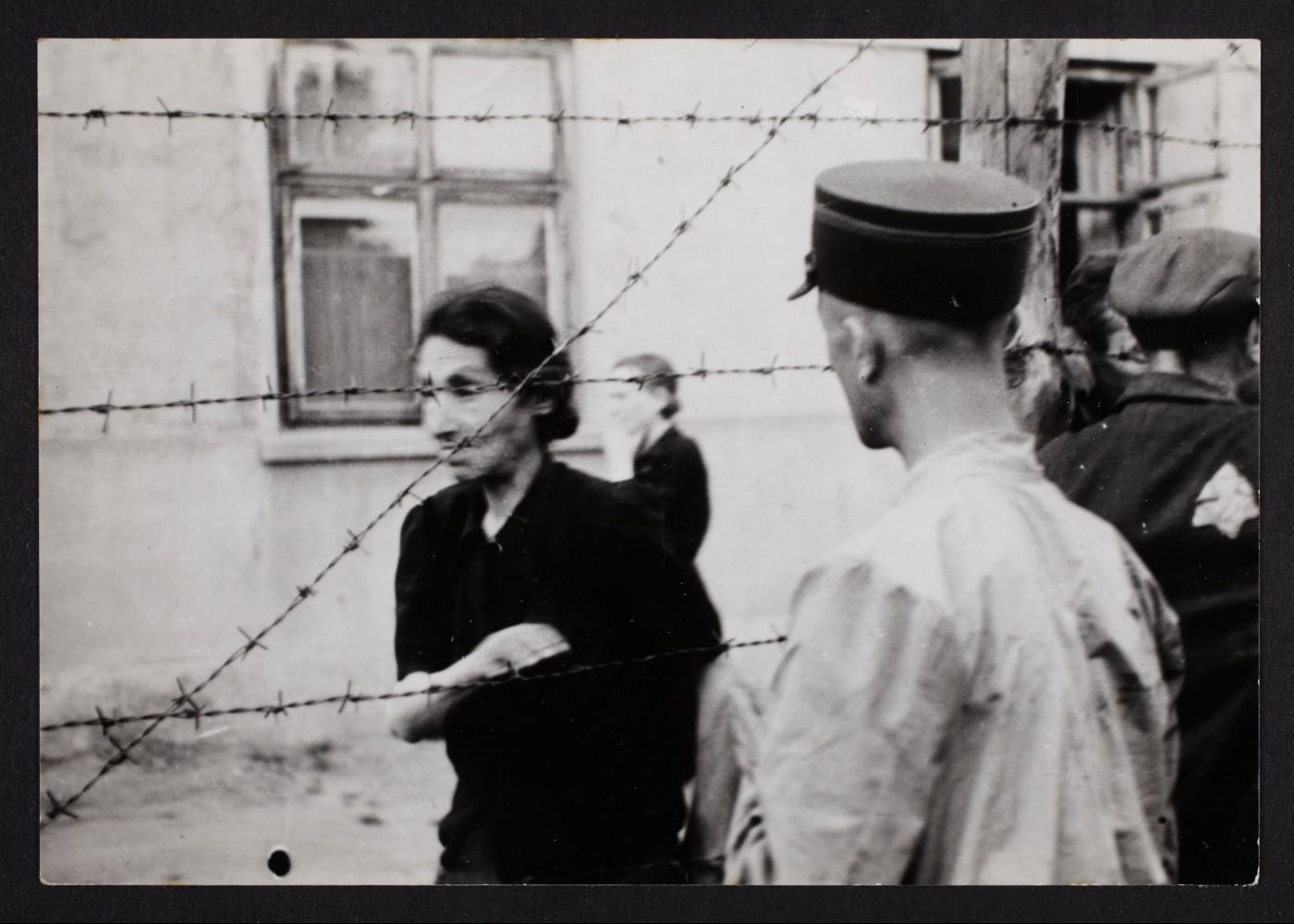 Henryk Ross, Ghetto police with woman behind barbed wire, 1940-1944