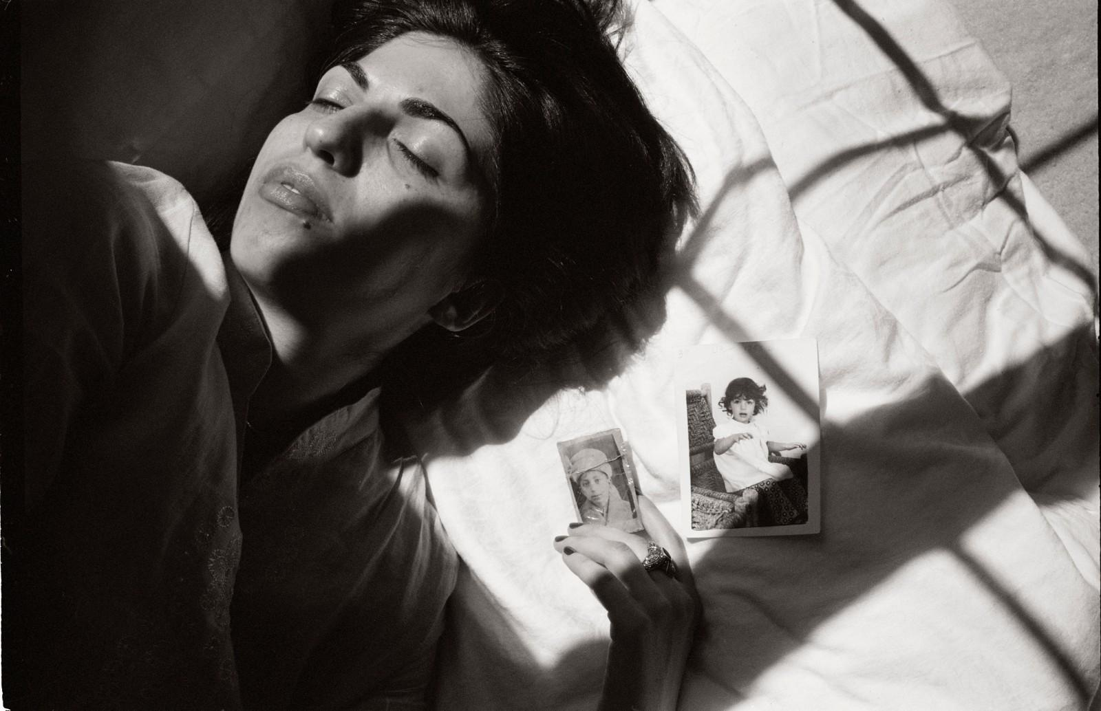 photograph of woman on a bed holding two photographs