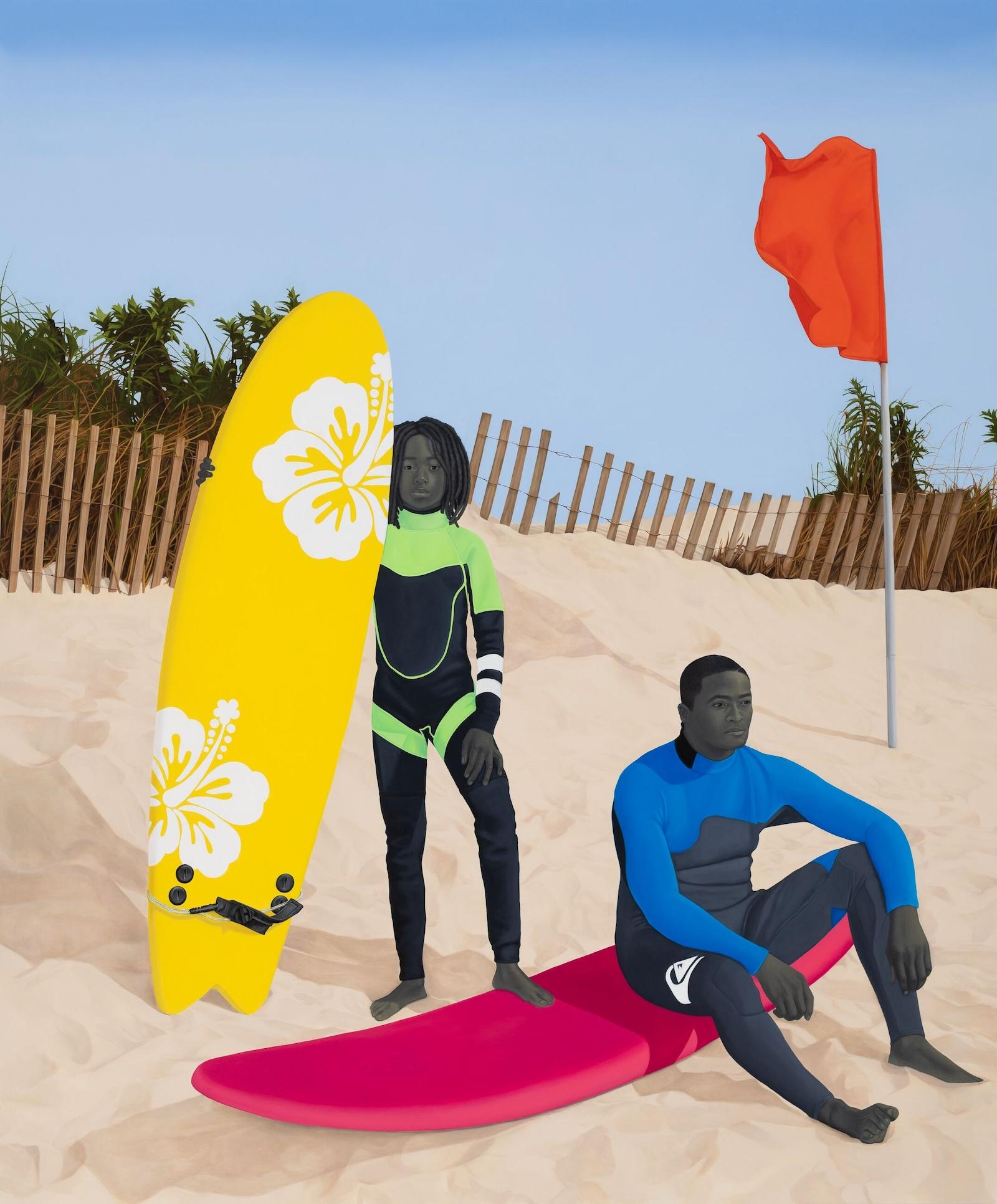 Two surfers pose, one stands with her board, looking at viewer while the other sits on his, looking out at the sea.
