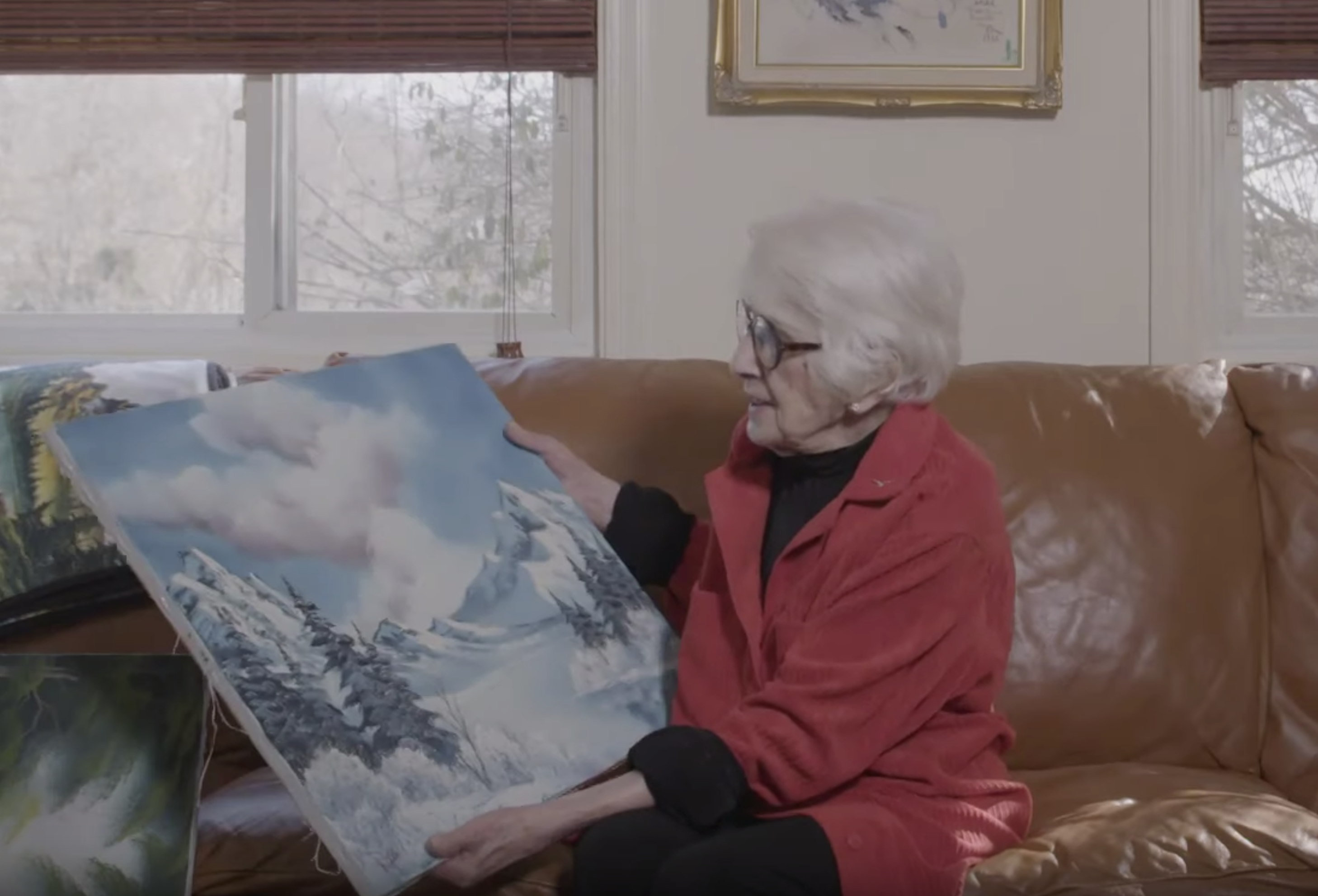 Woman holding bob ross painting on couch