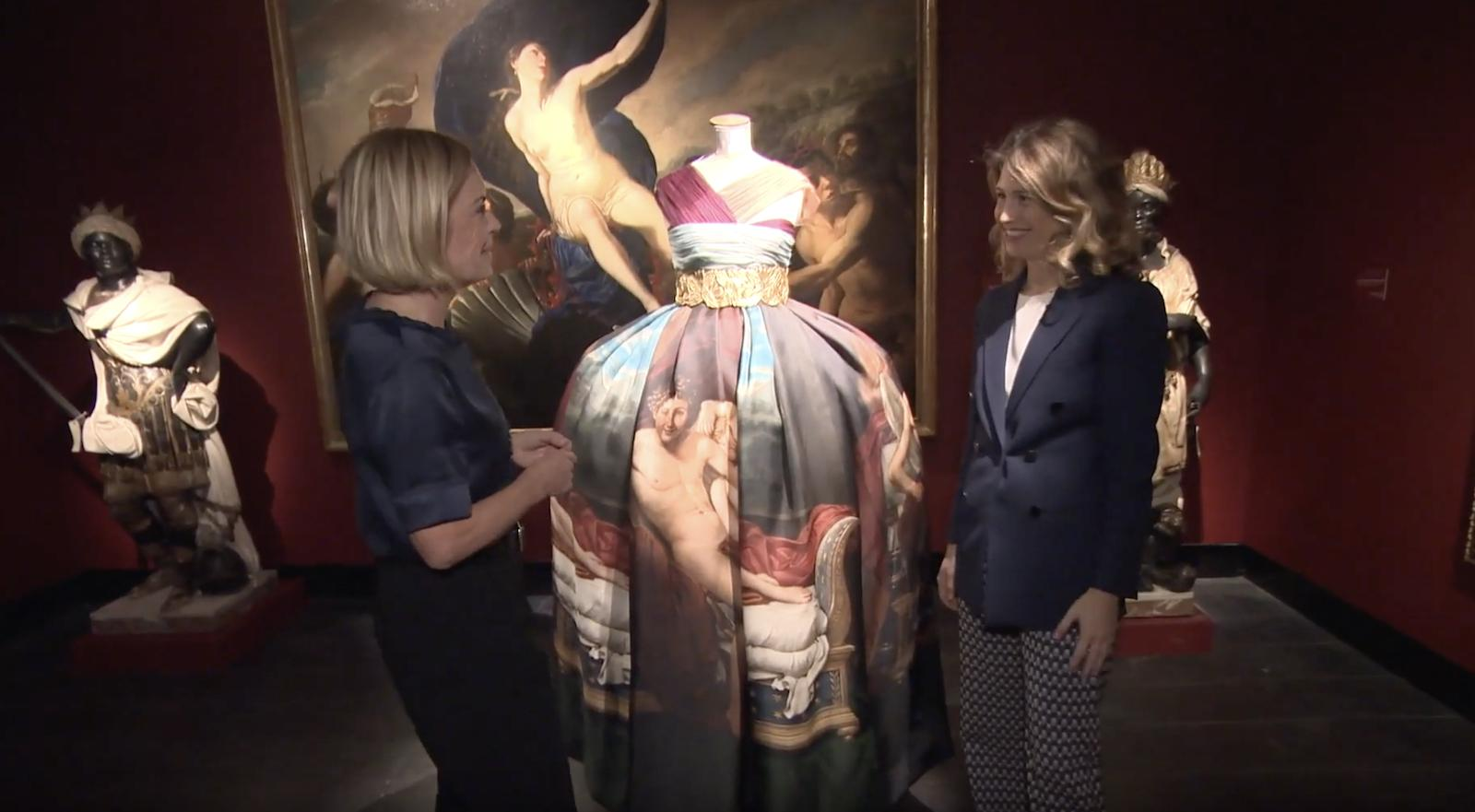 Examining dress with painting in background