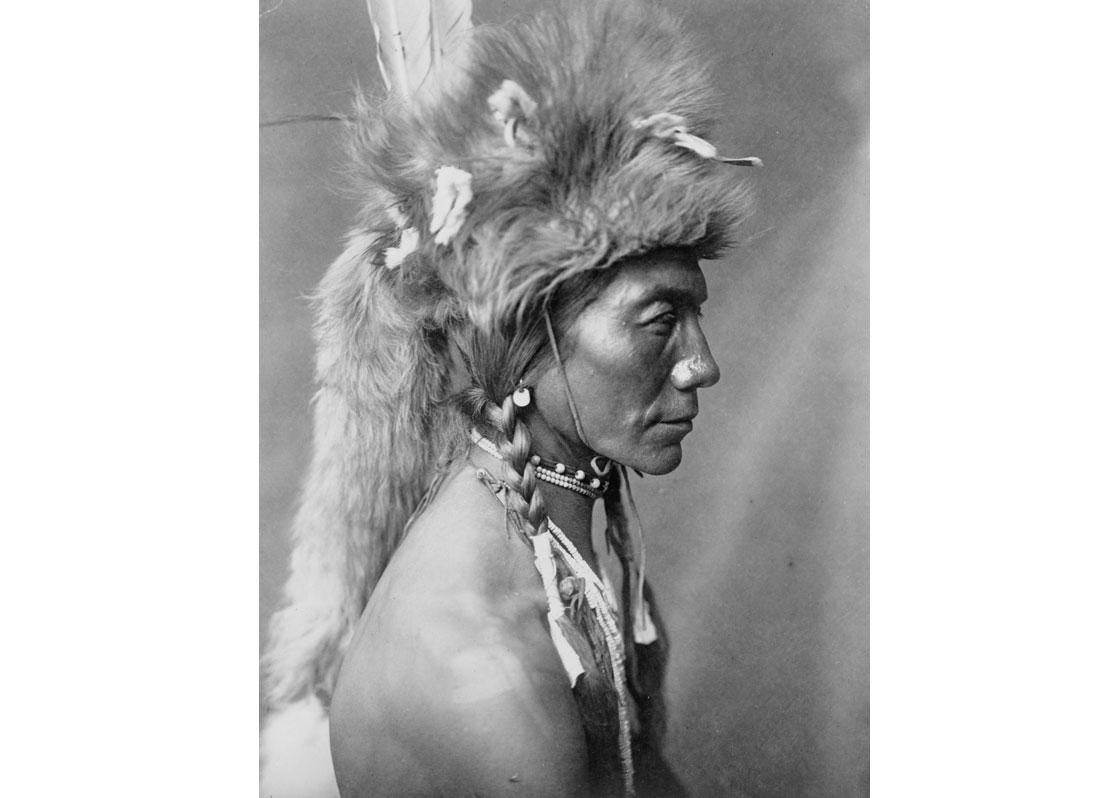 Yellow Kidney, Piegan man, head-and-shoulders portrait, facing left, wearing a fur headdress, 1910.