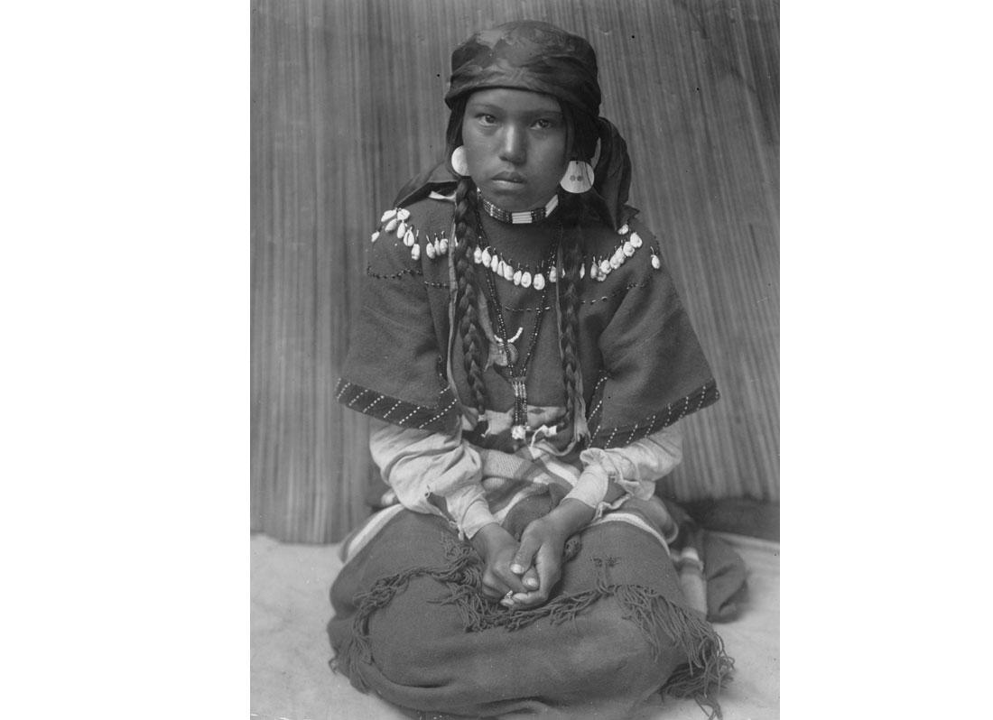 Touch her dress--Kalispel. Kalispel girl sitting on her knees, hands folded in lap, 1910.