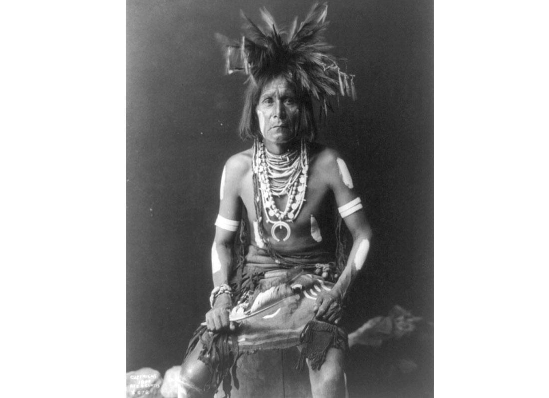 Snake priest. Native American man seated, three-quarter-length, facing front, 1900.