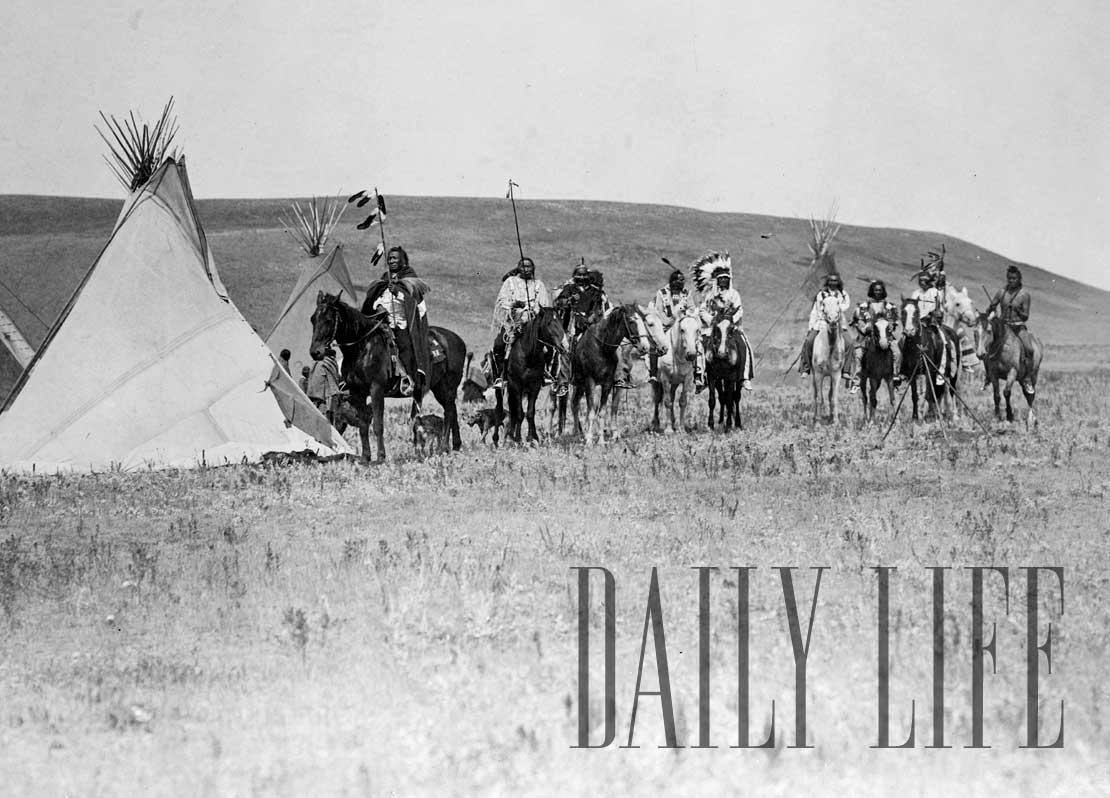 Landscape with four tipis, eleven Atsina Indians on horseback, three women, a child, and two dogs, Montana, 1908.
