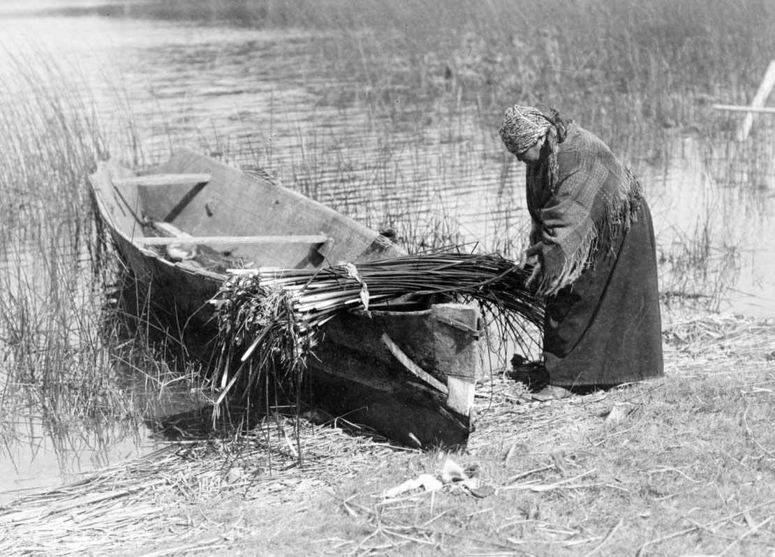 Cowichan woman putting tule on boat, 1910.