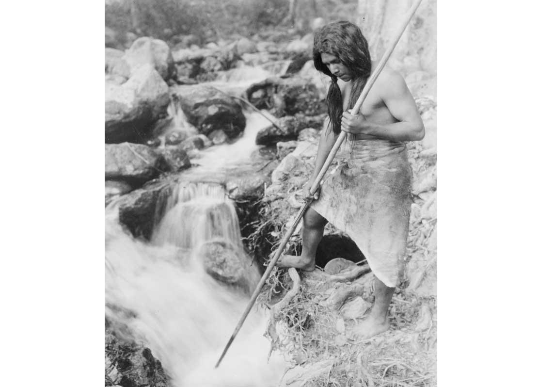 Hupa man with spear, standing on bank gazing into stream, 1923.