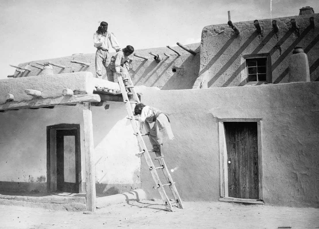 Three Tewa Indians, two on roof of adobe building, one on ladder, San Idlefonso, New Mexico, 1927.