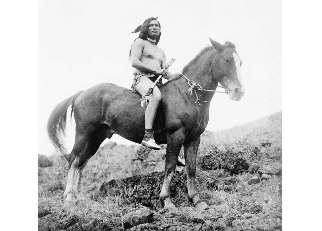 Nez Percé man, wearing loin cloth and moccasins, on horseback, 1910.