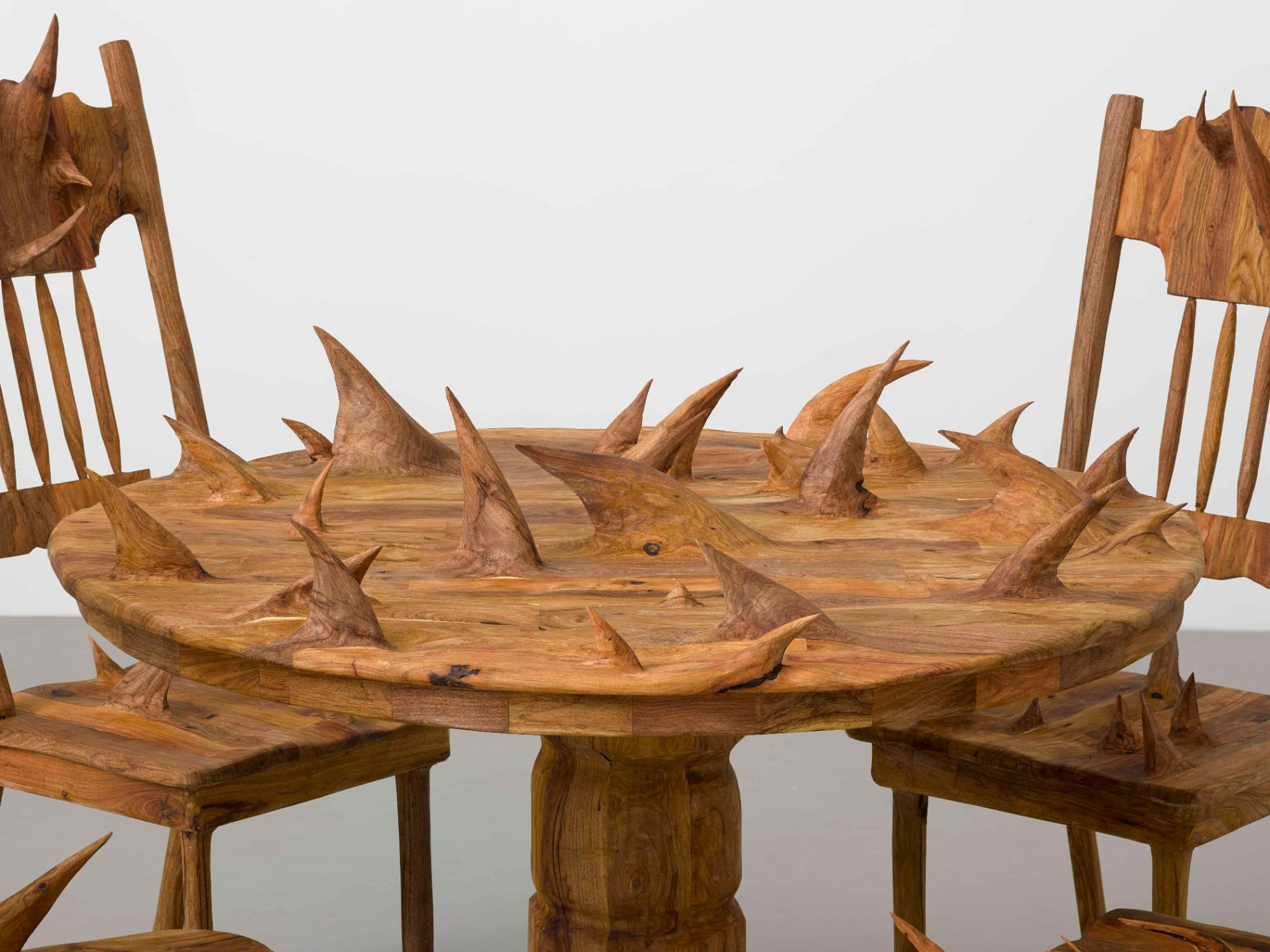 a circular wooden table and chairs, all covered in large thorny protrusions