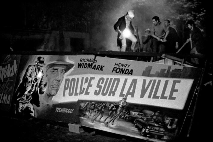 "BRUNO BARBEY black and white photograph of men standing atop a street barricade in France made of movie posters for ""police sur la ville"""