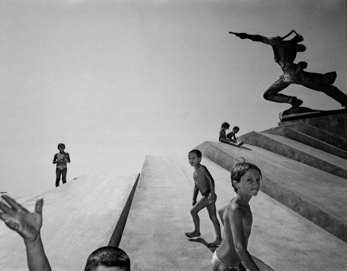 CARL DE KEYZER black and white photograph of a children playing beneath a statue