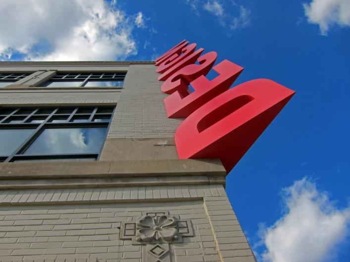 "the word ""design"" in large red letters runs up the corner of a building toward the bright blue sky"