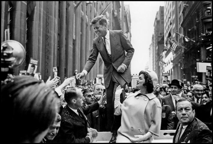 Cornell Capa photograph of JFK standing on a platform shaking hands with men in the crowd below him with Jacqueline Kennedy looking up at him