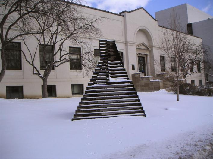 a white building in the snow with a black geometric sculpture in front of it