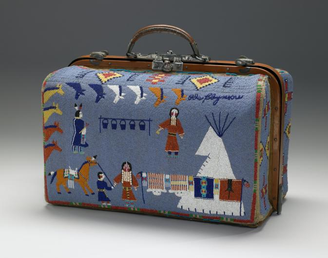 A small suitcase covered in beaded imagery of a native american life, including horses, teepee, and figures in traditional attire