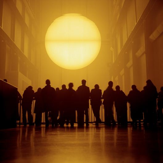 PETER MARLOW photograph of crowds standing before an Olafur Eliasson installation of a large, bright sun in the Tate Modern art museum
