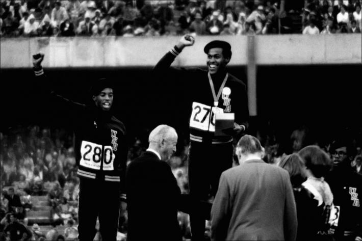 Raymond Depardon black and white photograph of American athletes Larry James, Lee Evans and Ron Freeman on the winner's podium for the 400-meter relay at the 1968 Olympic Games