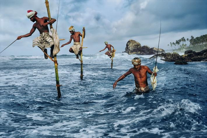STEVE MCCURRY photograph of Sri Lankan fisherman on stilts in the ocean