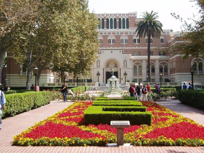 USC hall with many red flower beds and sidewalks